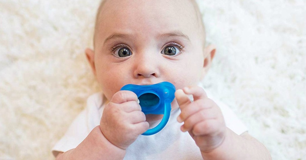 baby holding onto a pacifier that it's sucking on