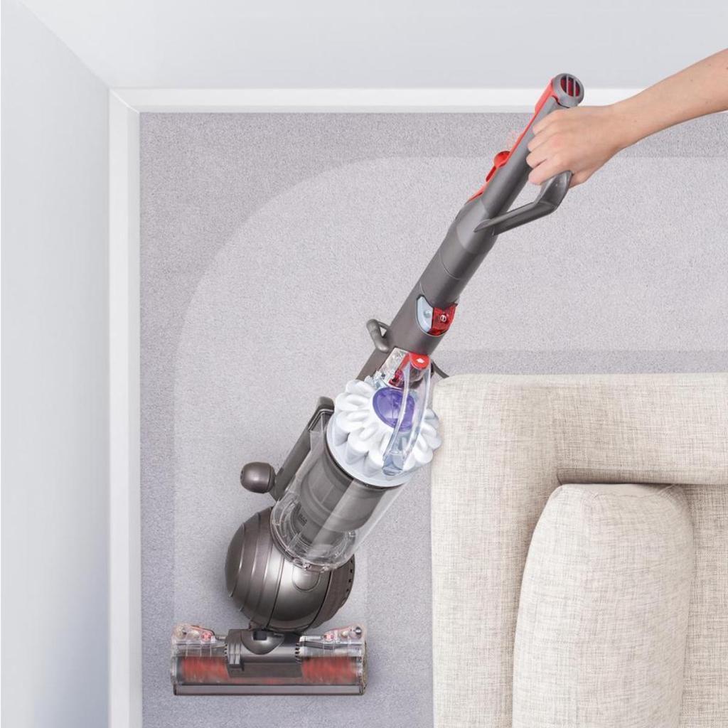 hand using Dyson Slim Ball Multi-Floor Upright Vacuum Cleaner in White on carpet