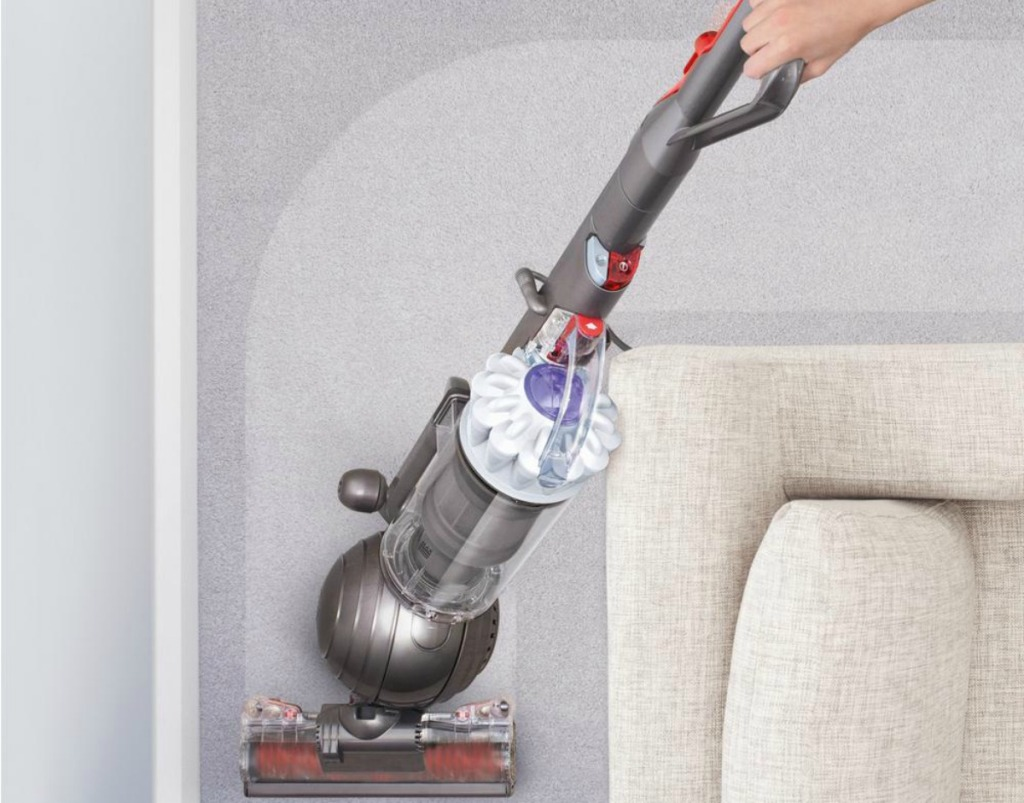 woman pushing vacuum cleaner around a couch corner