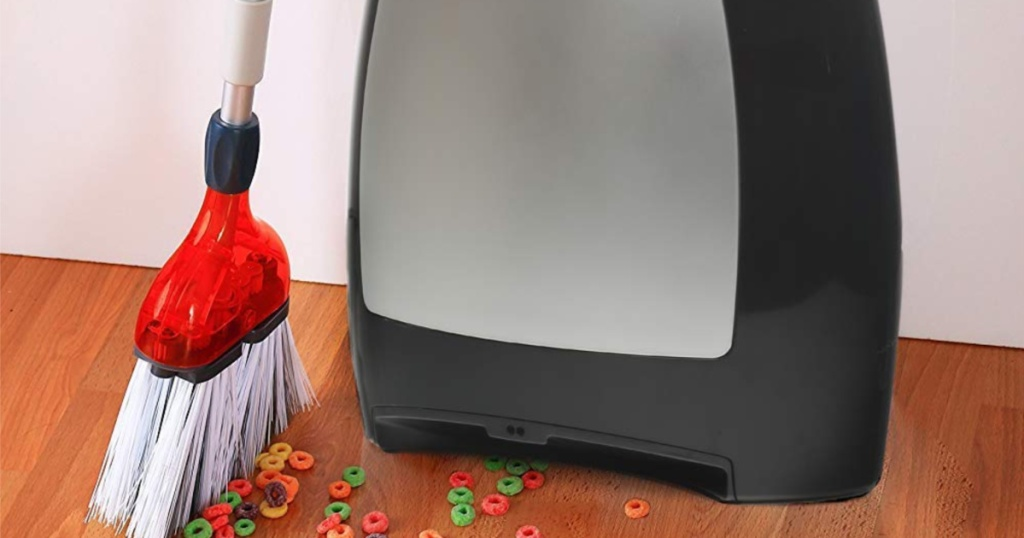 broom sweeping cereal into an automatic vacuum