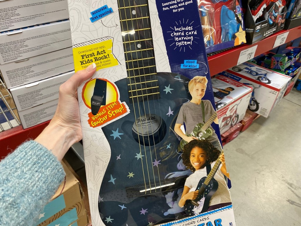 woman holding First Act Acoustic Guitar in box