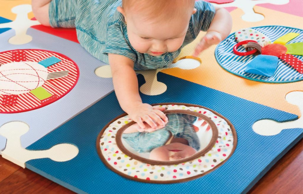 baby laying on mat playing with Funspot Playspot Activity Circles