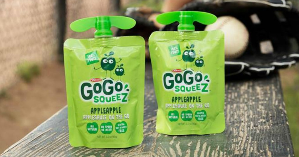 Two pouches of applesauce on a bench near baseball gear