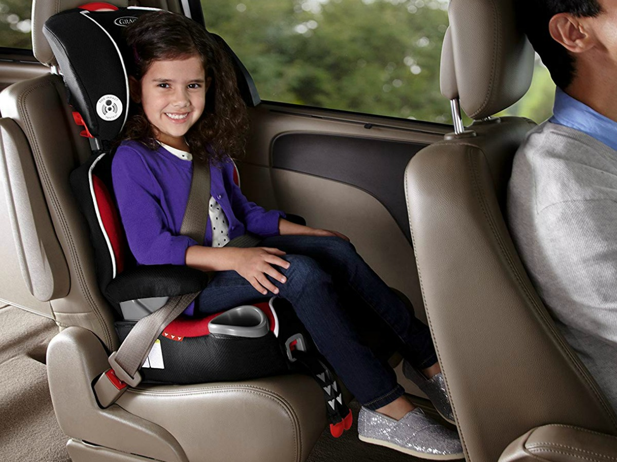 Young girl sitting in a booster seat in the backseat of a vehicle