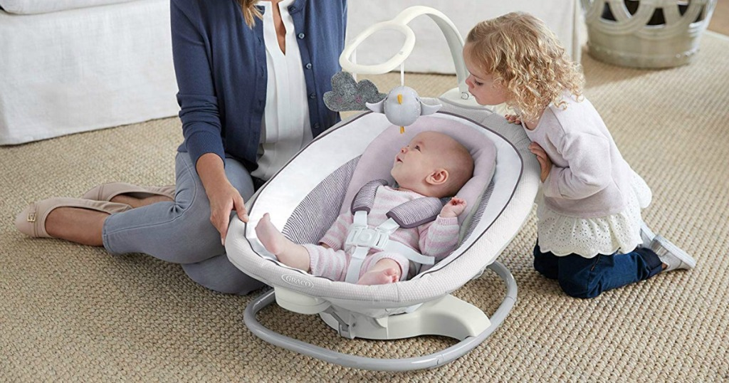 Baby in portable seat with mom and sister on floor