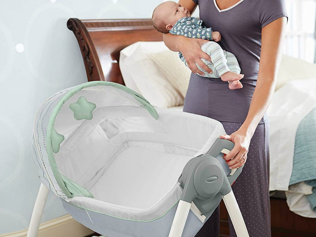 Woman holding a newborn and setting up a bassinet in bedroom