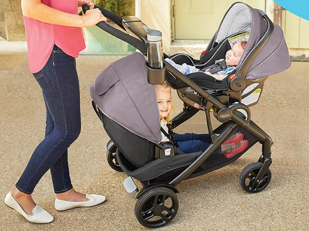 Mom pushing stroller with two young children inside