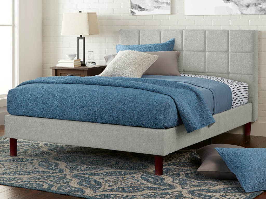 Gray upholstered bed with blue bedding