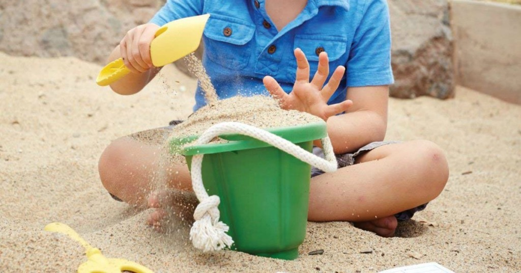 boy playing with Green Toys Sand Kit