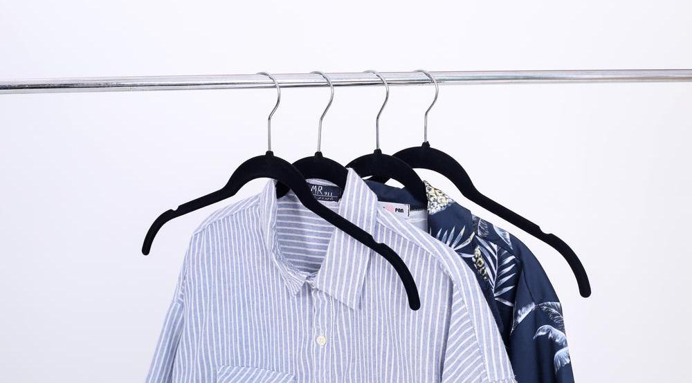 hangers on rack with shirts on them