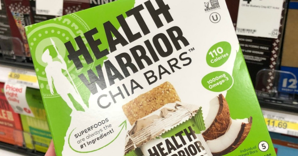 Box of coconut flavored chia bars in hand near in-store display