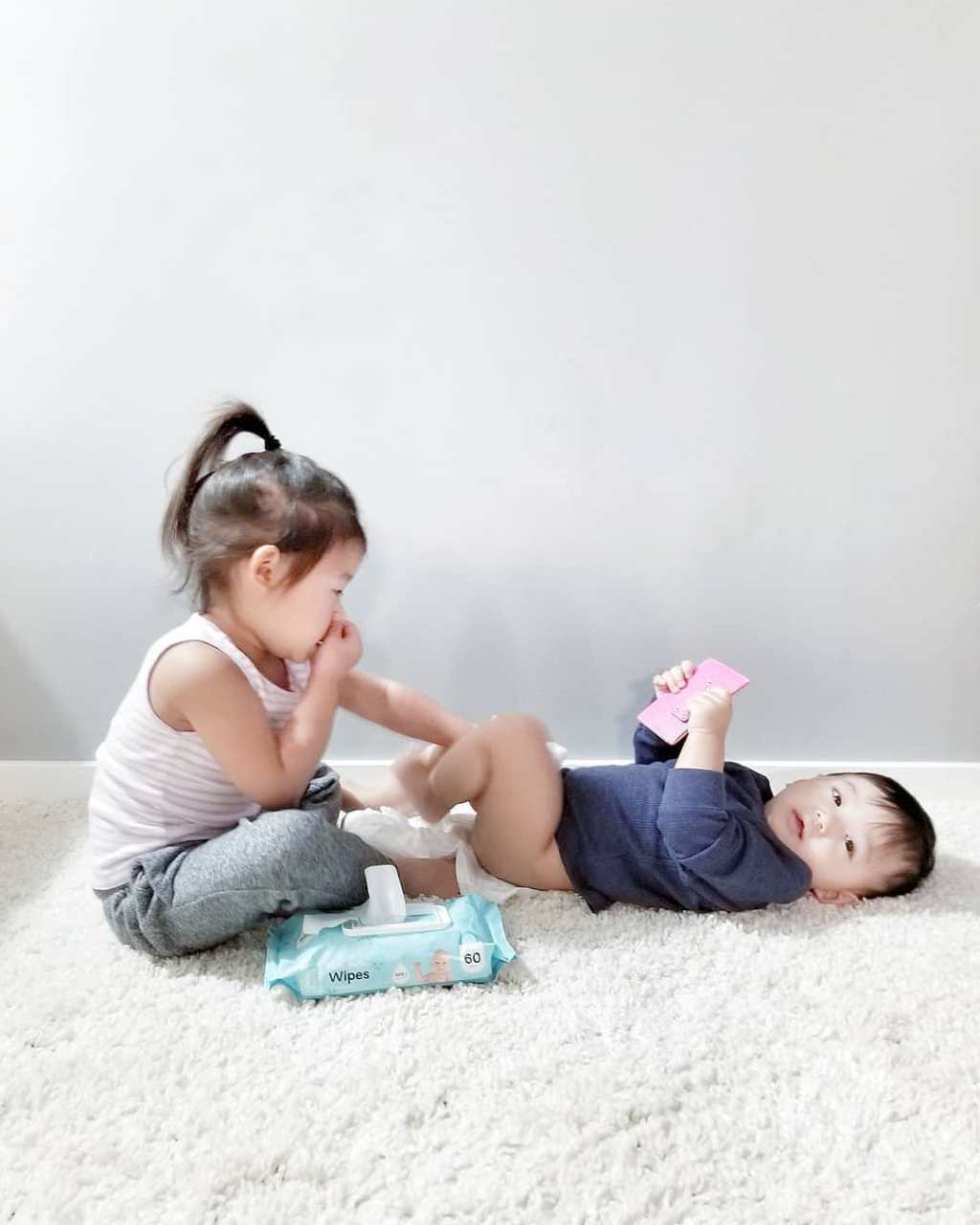 Toddler cleaning baby with Hello Bello Wipes