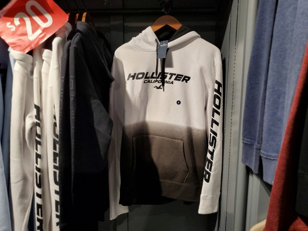 white hollister guys hoodie hanging up in the store