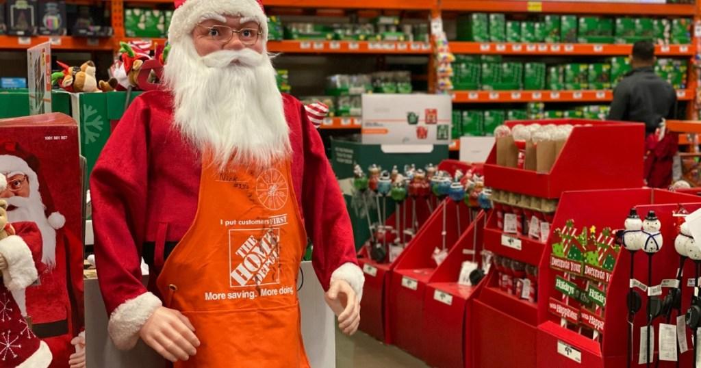 Santa near Christmas decorations wearing Home Depot apron