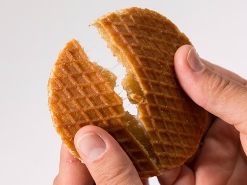 person breaking open a Honey Stinger waffle snack