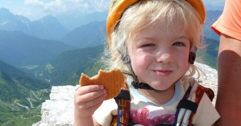 little girl in helmet eating a Honey Stinger waffle