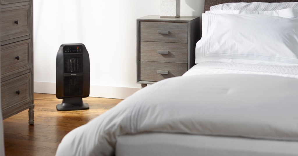 black space heater in bedroom with bed and bedroom furniture in room