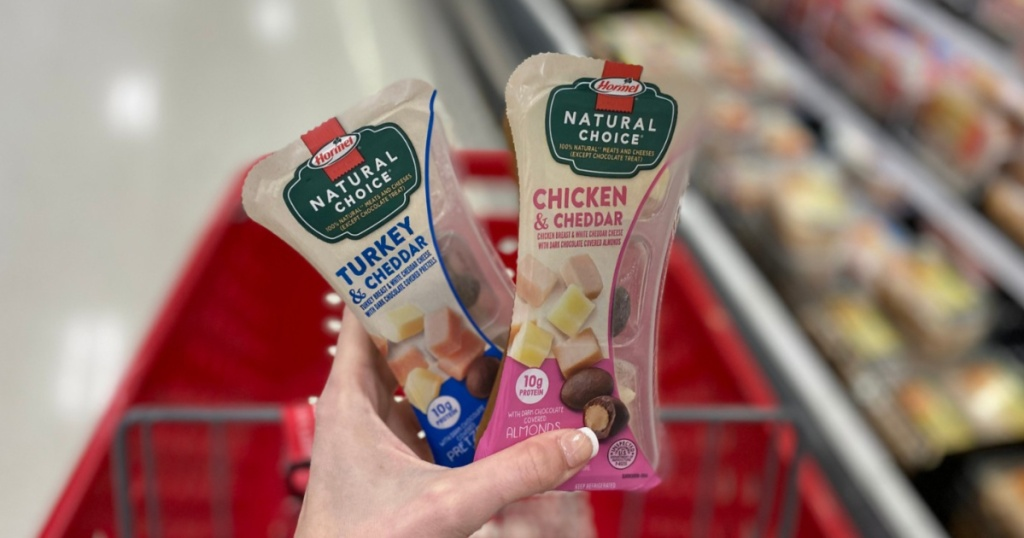 hand holding hormel natural choice turkey and chicken and cheddar snacks with target cart in background