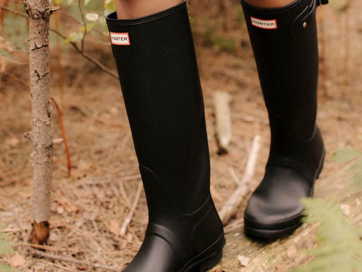 woman walking through woods in black tall hunter boots