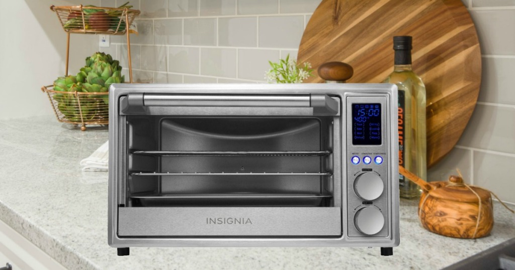 Insignia 6-Slice Toaster Oven on counter near olive oils and cutting boards