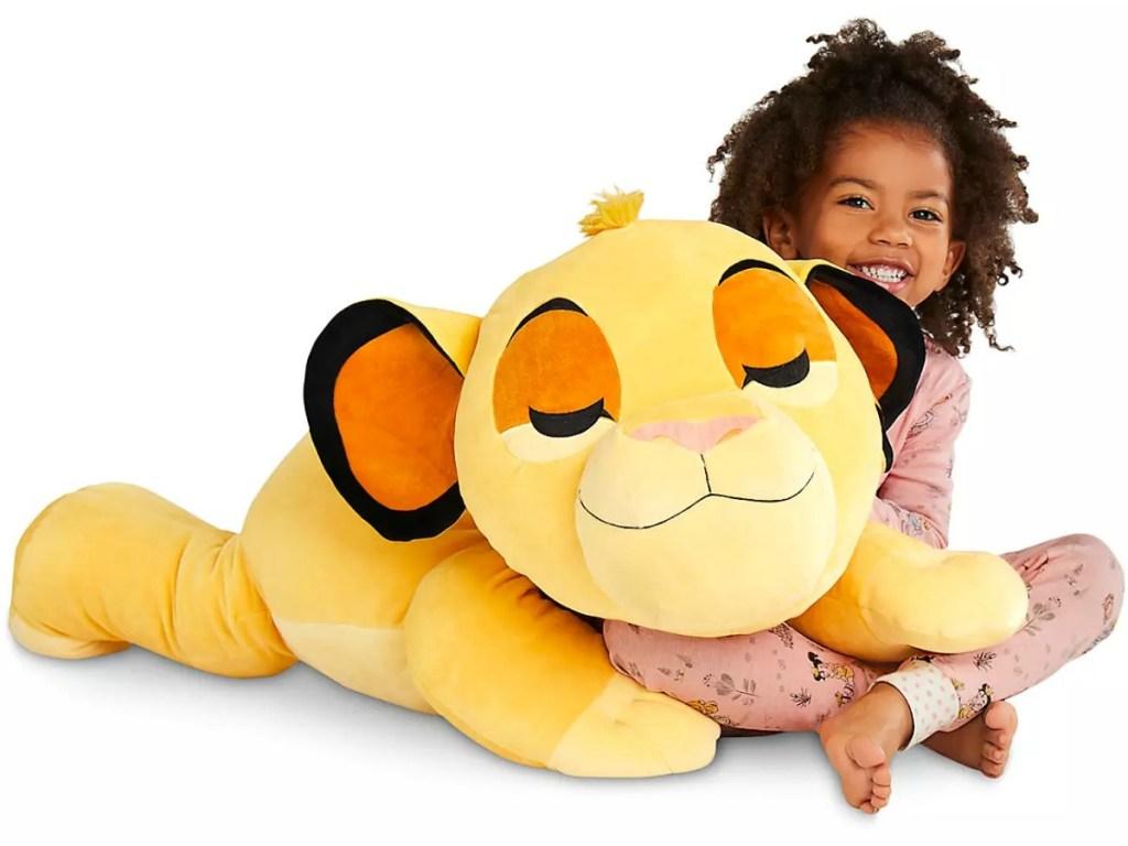 Girl sitting with a Jumbo 30-Inch Simba Cuddleez Plush