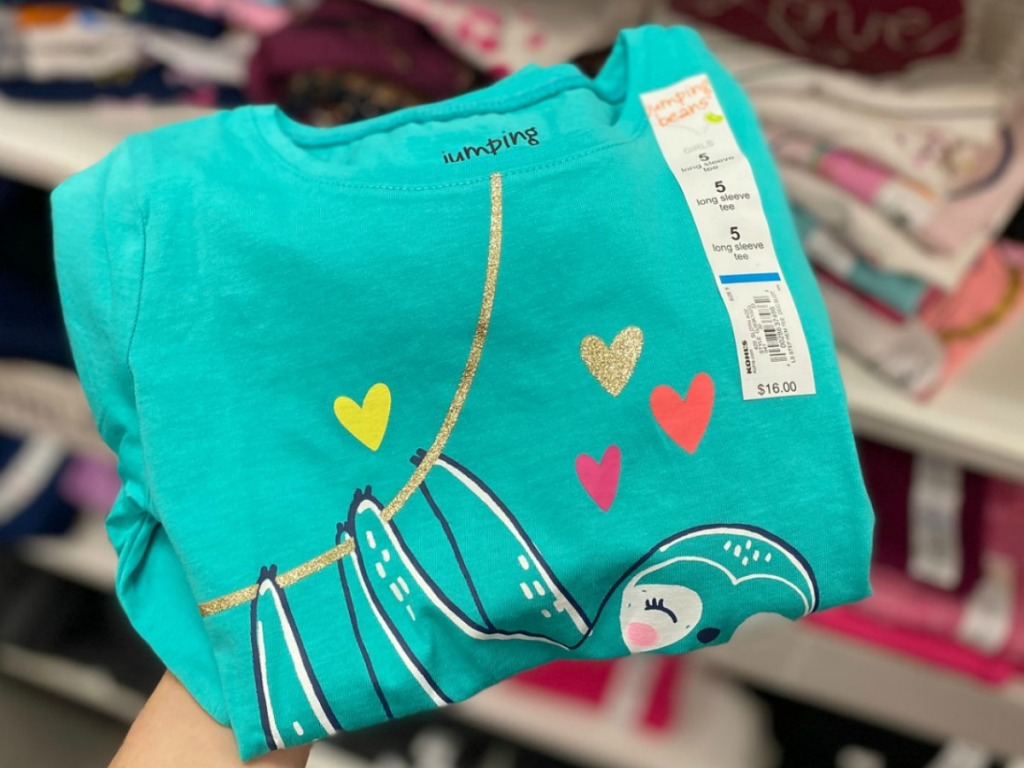 Girls graphic tee folded in hand with sloth design