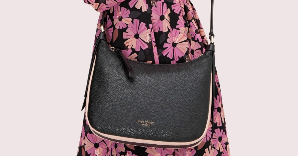 black handbag being worn by a woman with a floral dress on
