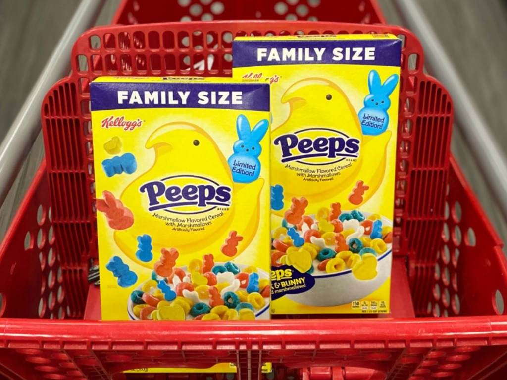 Two boxes of Peeps themed cereal in family size sitting in seat of red shopping cart, in store