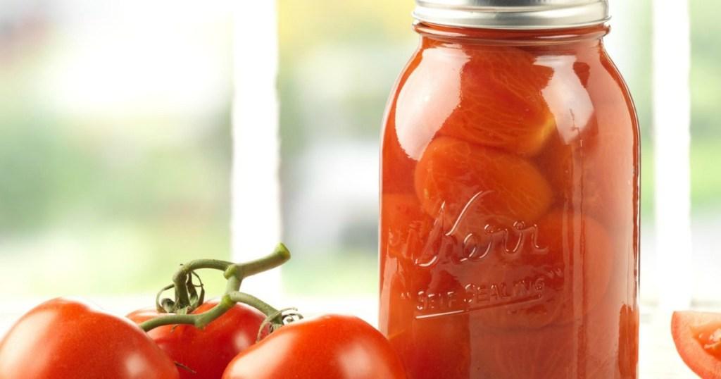Kerr brand glass mason jar filled with stewed tomatoes near window sill