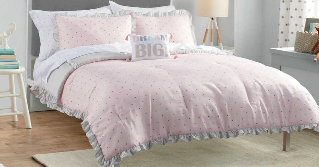 Large bed made with a pink ruffle quilt with matching pillows