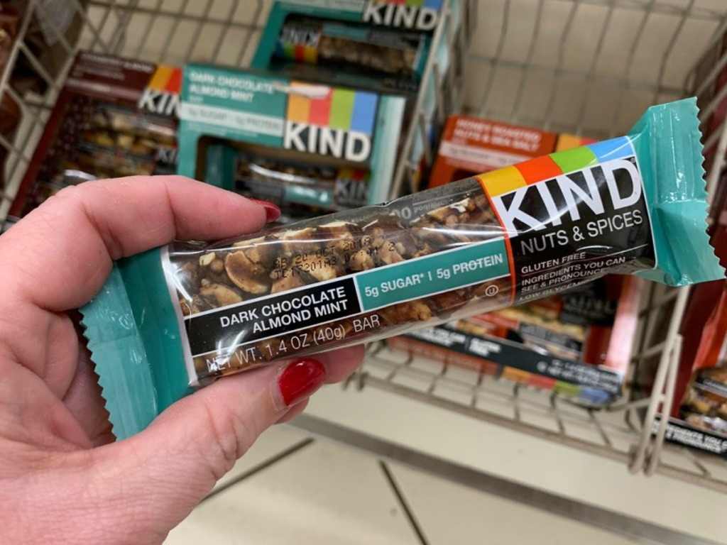 lady holding a Kind bar at the store