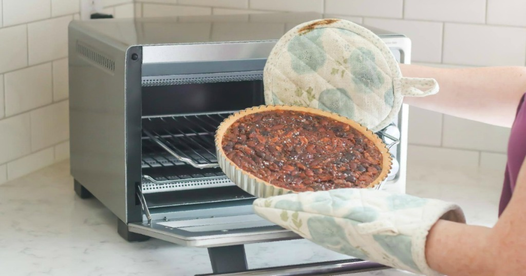 Woman taking a savory tarte out of a convection oven