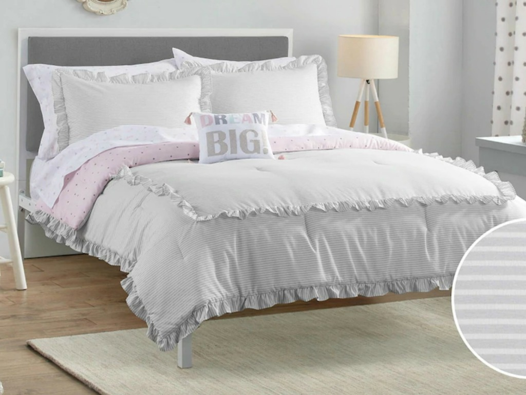 Large kids bed made up with gray and pink ruffle bedding with matching pillows