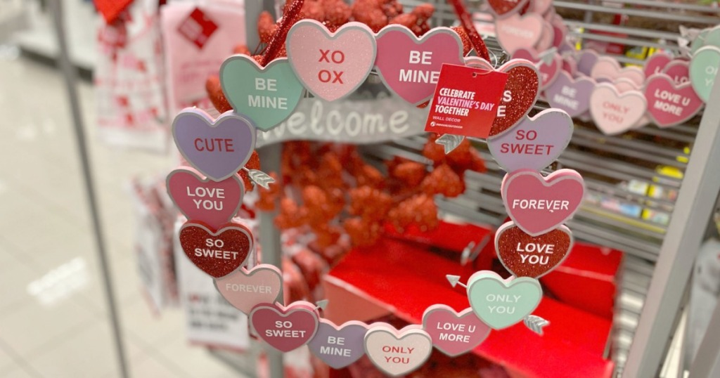 Valentine's Day candy heart themed wreath in hand near in-store display