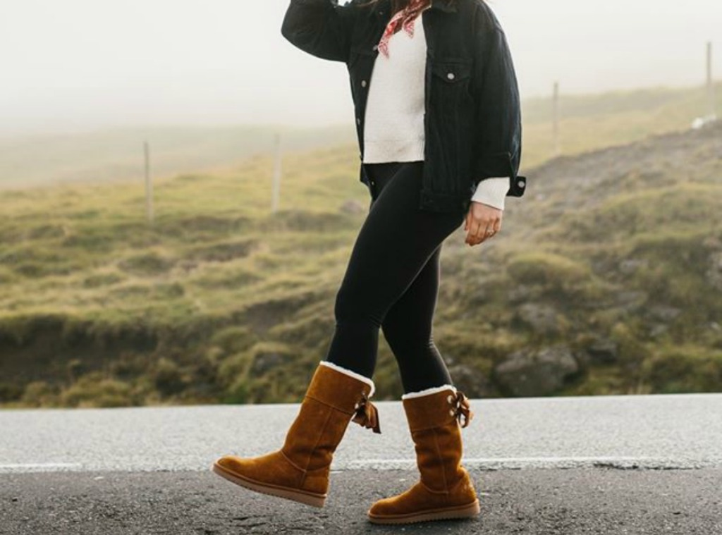 woman walking down a road wearing brown suede boots with bows in the back