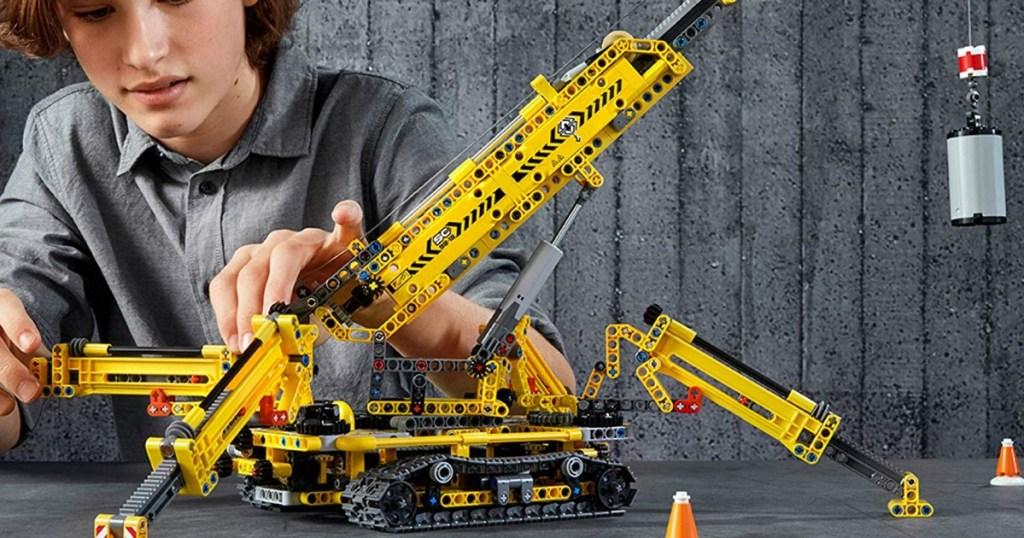 boy playing with a LEGO crane set