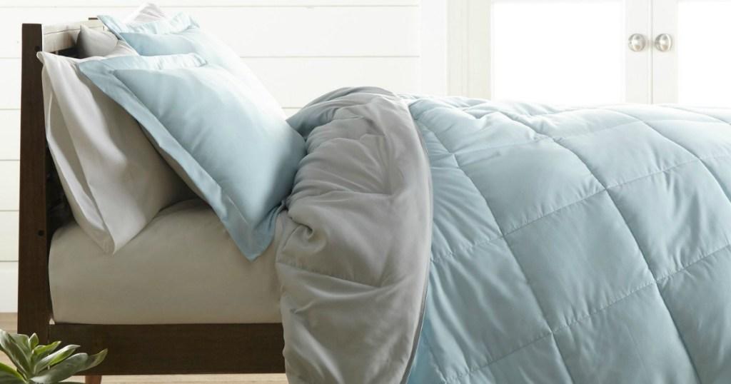 Reversible comforter in light blue on bedspread