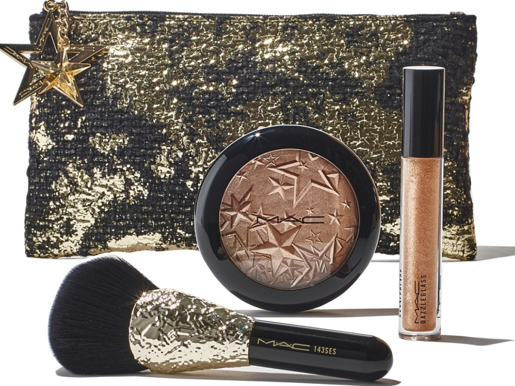 gold bag with mac bronzer, brush, and lip gloss outside bag