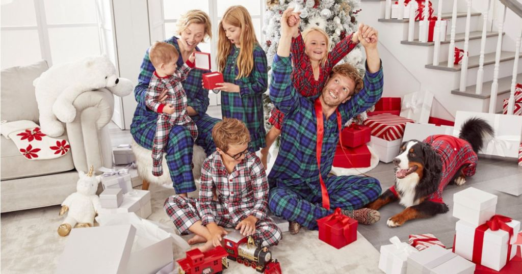 family in blue, red, and multicolor plaid family pajamas with christmas tree