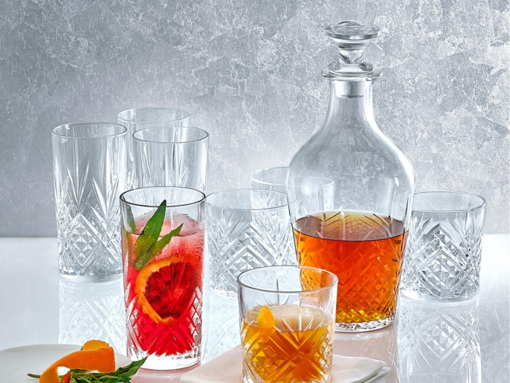 tall and short glasses with a decanter half filled with liquid