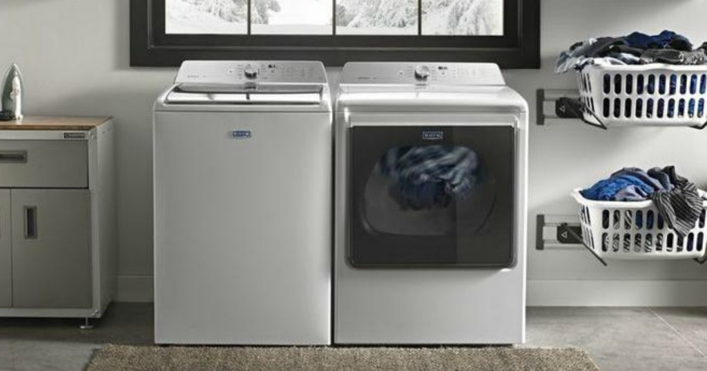 White washer and dryer in laundry room near storage