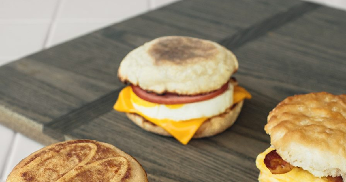 McDonald Egg McMuffin on cutting board with two other breakfast sandwiches