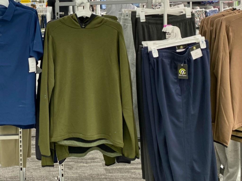 Men's hoodie in green on display in-store near athletic apparel