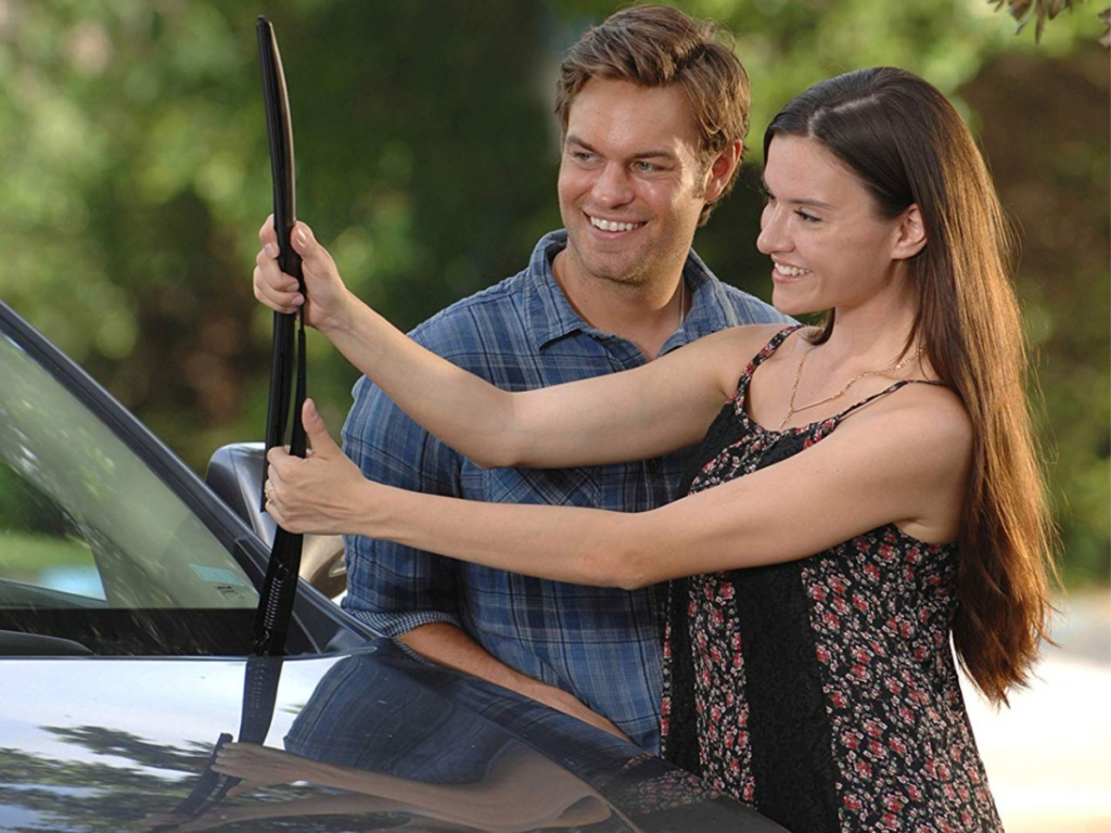 man and woman putting wiper blade on car