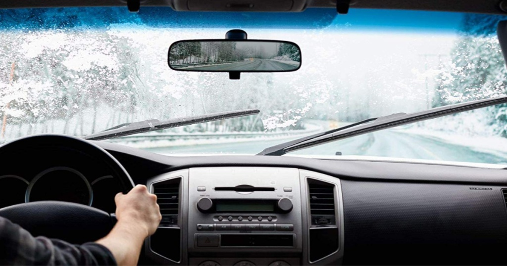 view of wiper blade being used during snow from inside of car
