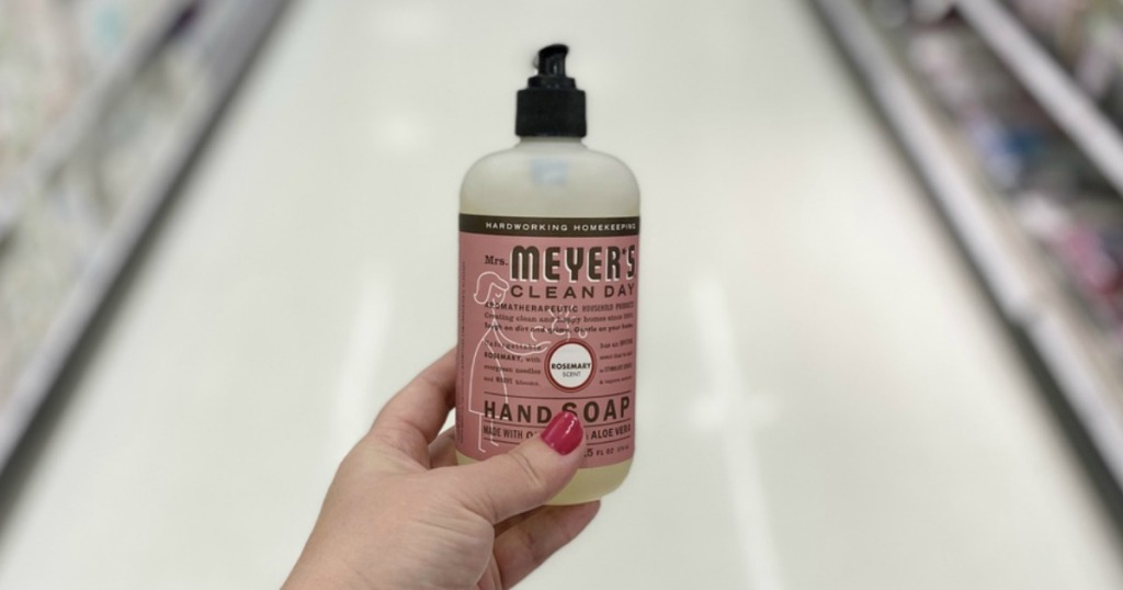 woman holding a bottle of Mrs. Meyer's Rosemary hand soap