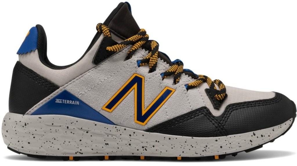 Boys brown tennis shoe with orange and black N symbol