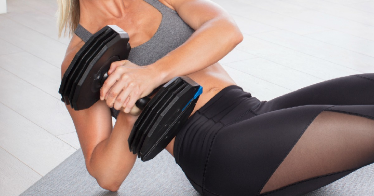 woman working out with an adjustable dumbbell