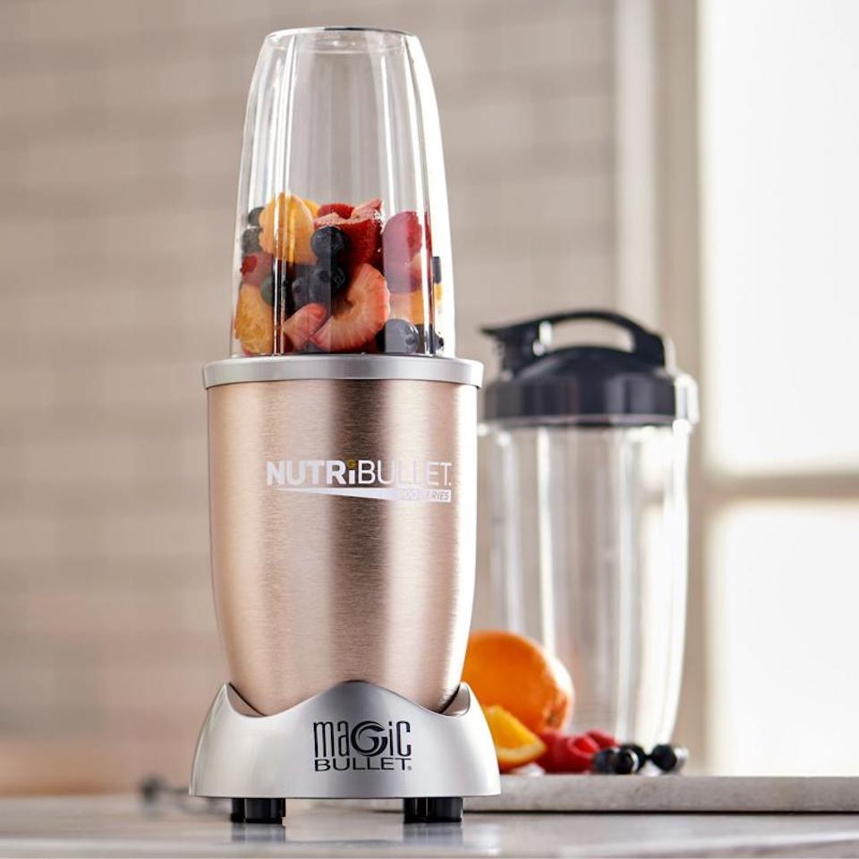 Nutribullet with fruit in it next to a cup