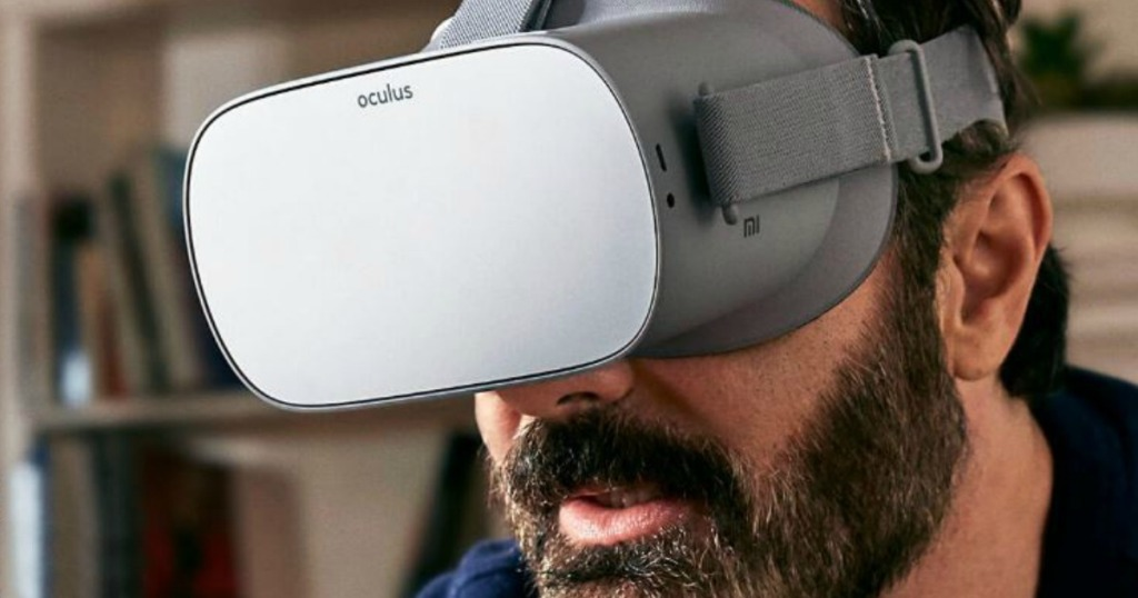 man with beard wearing VR headset over his eyes in front of bookcase